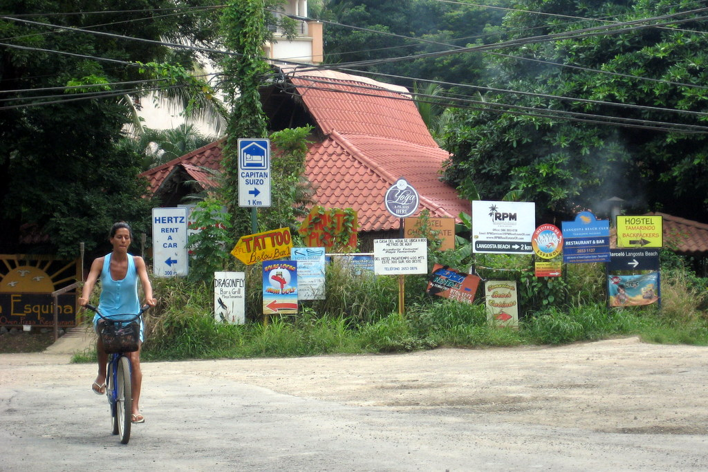 Costa Rica Travel Guide 201 Signs at Tamarindo Beach, Costa Rica with girl on bike