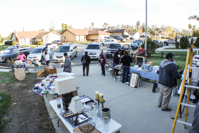 Garage sale with lots of cars and people buying everything