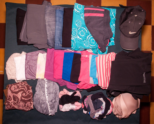 Packing list for a girl's clothes all laid out on table