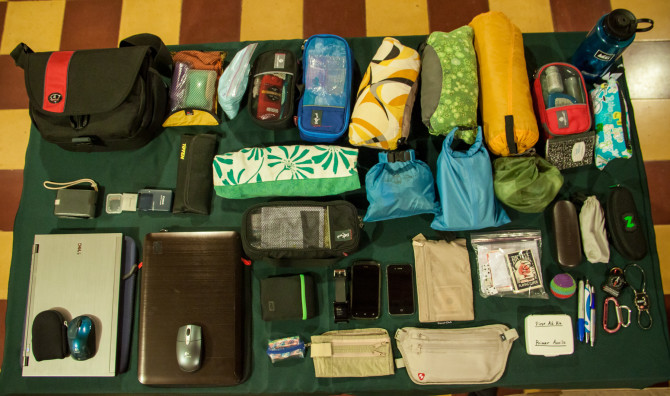 Table filled with our entire packing list including clothes, laptops, camera
