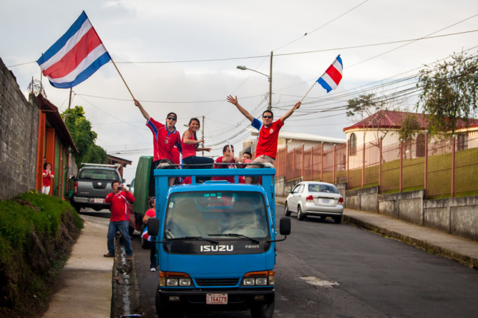 Costa Ricans Waving Flags from a truck