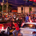 Crowds of people rocking cars celebrating Costa Rica winning world cup