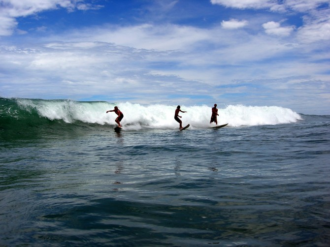Surfers Riding a wave in Costa Rica at Manuel Antonio beach