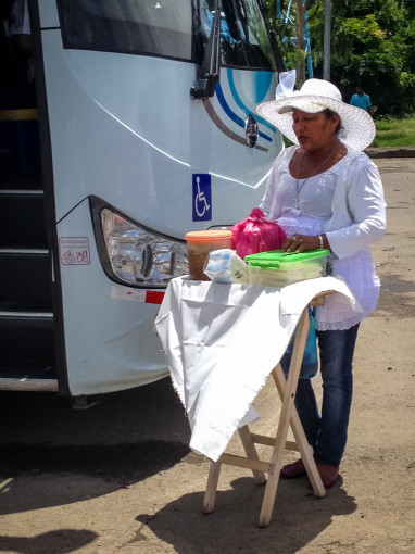 Lady selling food by bus