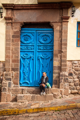 Alyssa Sitting by Blue Door in Cusco