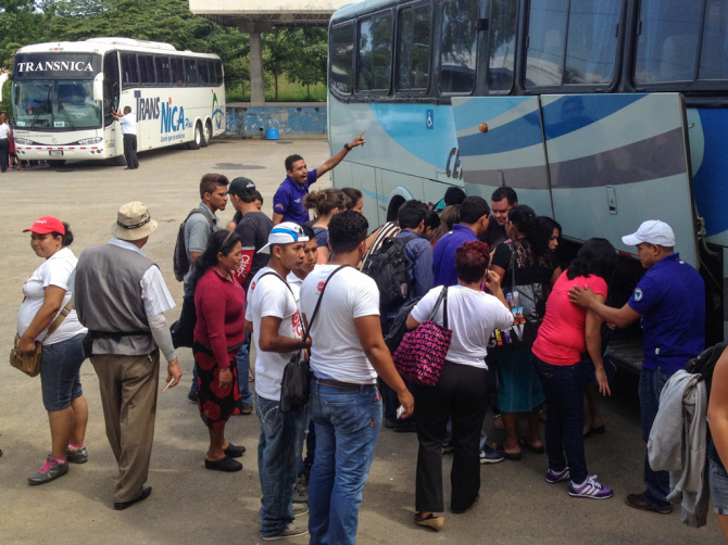 Unloading bags from a bus with a big crowd of people watching to avoid tourist scams