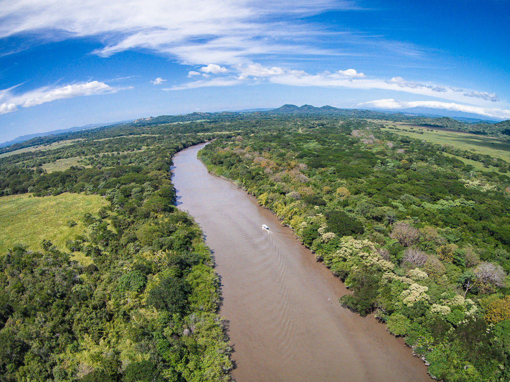 Boat on the Tempisque river with jungle in the background and blue sky