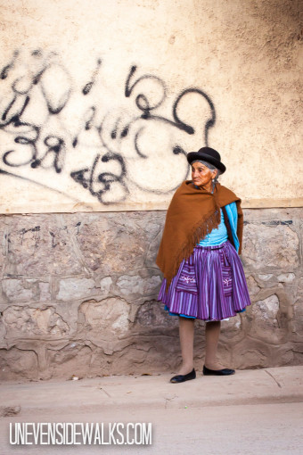 Indigenous lady in Bolivia Standing on the Uneven Sidewalk