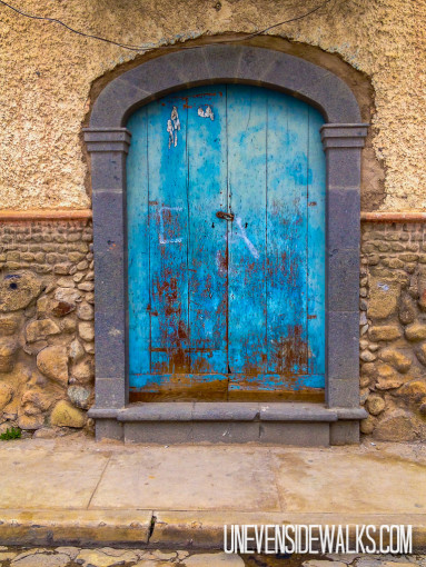 Blue arched door that's pretty beat up