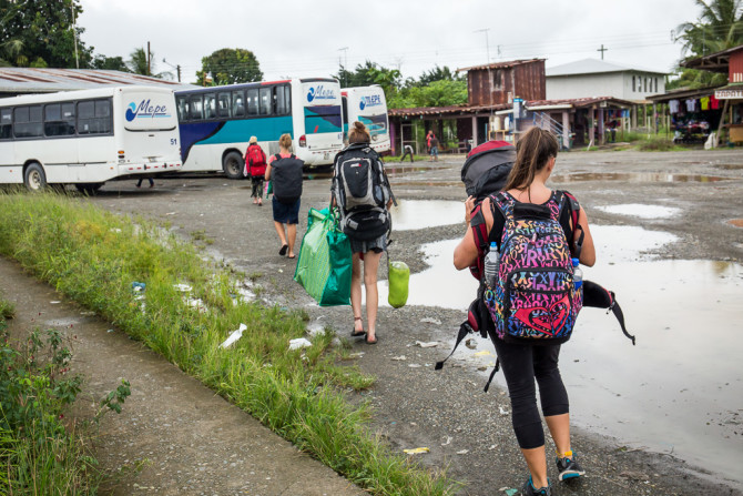Travelers with Big Backpacks Boarding a Bus